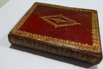 Repaired book with board reattached and corners repaired with leather